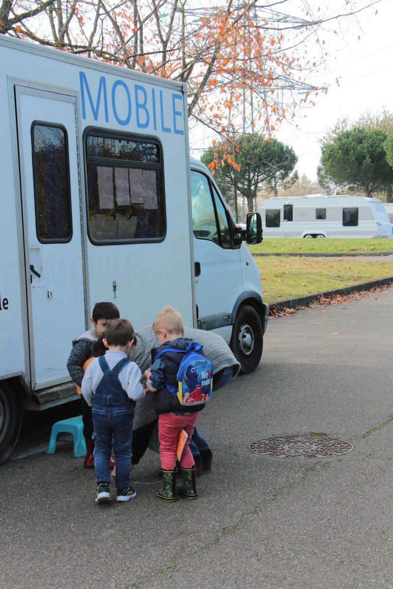 C'est la fin de la matinée de classe ; l'enseignante raccompagne les enfants jusqu'à leur caravane.